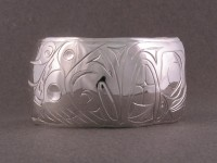 photo of Hand carved sterling totem bracelet showing the bear and the salmon